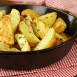 Fresh potatoes fried in a pan on a wooden table — Stock Photo #10747419