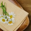 Wooden plate and daisy on wooden background — Stock Photo