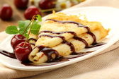 Sweet pancake with chocolate sauce and cherries — Stock Photo