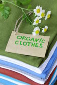 Stack of colorful clothing with organic label — Stock Photo