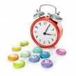 Stock Photo: 3d illustration: big red alarm clock with group of vitamins.
