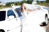 Young bride standing beside a limousine — Stock Photo