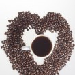 Stock Photo: Heart of coffee beans with cup of coffee in heart on white background