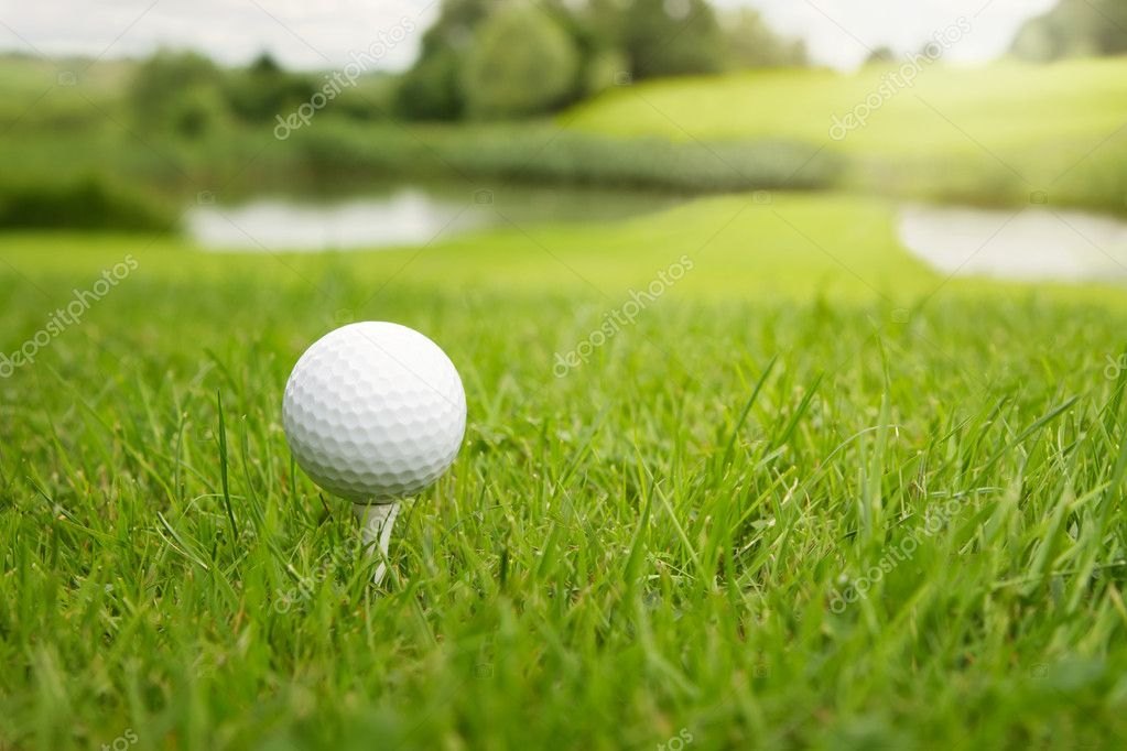 Golf ball on a tee against the golf course with copy space  — Stock Photo #11243614