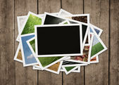 Stack of photos at wooden background — Stock Photo