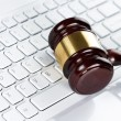 Gavel at the computer keyboard - Stock Photo