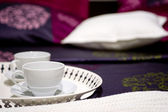 Two cups on a nice bed — Stock Photo