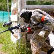 Paintball sport player takes cover in shelter — Stock Photo