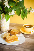 Honeycomb with a cup of tea and a bouquet of blooming Jasmine — Stock Photo