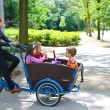 Young girl transporting children in cart . Amsterdam. Nether — Stock Photo #12338058