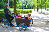 Young girl transporting children in the cart . Amsterdam. Nether — Stock Photo