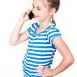 Little girl speaking by cell phone, white background — Stock Photo