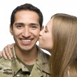 Royalty-Free Stock Photo: Woman Kisses Latino Serviceman on the Cheek