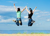 Two happy women jumping on the beach — Stock Photo