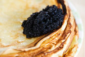 Pancakes with black caviar — Stock Photo
