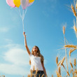 Teen girl at a wheat field with balloons — Stock Photo #11417790