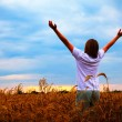Young man staying with raised hands at sunset time — Stock Photo
