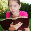 Teen girl reading the Bible outdoors — Stock Photo