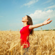 Teen girl staying at a wheat field — Stock Photo