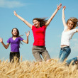 Teen girls jumping at a wheat field — Stock Photo