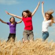 Teen girl jumping at a wheat field — Stock Photo