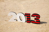 Wooden 2013 year number on the sand — Stockfoto