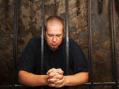 Young man behind the bars — Stock Photo