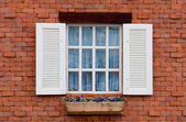 Vintage window on red brick wall — Stock Photo