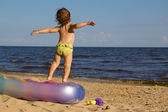 Little girl jumping to the sea side — Stock Photo