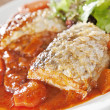 Stock Photo: Fish with tomato sauce and green leaves