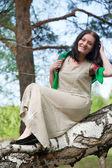 Beautiful woman on birch — Stock Photo