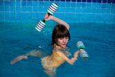 Attractive girl trains in aqua aerobics — Stock Photo
