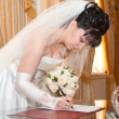 Stock Photo: Pretty bride signing document