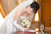 Pretty bride signing document — Stock Photo