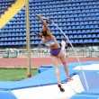 Girl competes in pole vault competition — Stock Photo