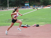 Girl competes in pole vault competition — ストック写真