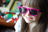 Portrait of beautiful young girl smiling with sunglasses. — Stock Photo