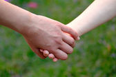 Child holds the hand of the mother on field — Stock Photo