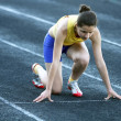 Athletic teenage girl in start position on track . — Stock Photo