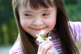 Portrait of beautiful young girl with flowers in the park — Stock Photo