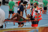Red Cross providing first aid to injured athlete on the 2012 IAAF World Junior Athletics Championships on July 12, 2012 in Barcelona, Spain. — Stock Photo