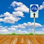 dřevěné kolo, cestě a znamení proti modré obloze — Stock fotografie