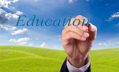 Main qui écrit le mot éducation — Photo