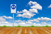 Wood walk way and sign against blue sky — Stock Photo