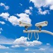 Surveillance cameras against blue sky — Stock Photo