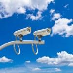 Surveillance cameras against blue sky — Stock Photo