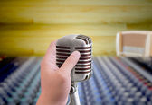 Hand holding microphone in sound record room — Stock fotografie