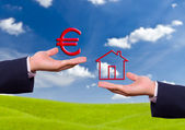 Hand exchange euro sign and house icon — Stock Photo