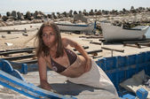 The beautiful girl and the old boats — Stok fotoğraf