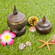 Thai spa bottle decorate with sea shell on the green grass — Stock Photo